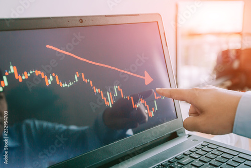 Fotografía  Hand of man point  to the laptop show financial market chart graphic going down