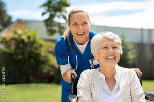 Fotografia  Woman on wheelchair having fun with nurse