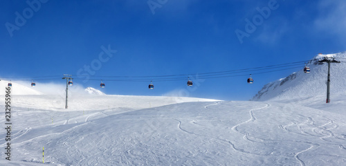 Panoramic view on gondola lift and off-piste ski slope in fog
