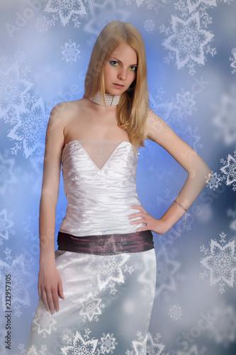 Fotografía  slender blonde in white evening dress on blue background in studio