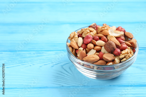 Fotografía bowl with different mixed nuts on a blue table