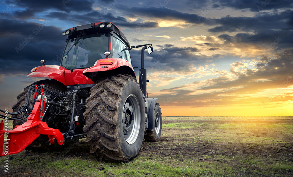 Fototapeta Agricultural tractor working in the field at sunset background