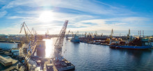 Aerial; Drone View Of Port With Shipyard Silhouettes On The Horizon; Industrial Cityscape In Sunny Weather With Blue Sky; Process Of Ship Repairing, Logistic Import Export And Transport Background