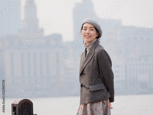 Fotografía  Beautiful young brunette woman in gray coat dress looking and smiling at you