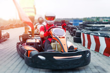 Go-Kart Racing Car On The Track In Action, Championship, Active Sports, Extreme Fun, The Driver Keeps His Hands On The Wheel. Driver Protective Gear. Day, Karting
