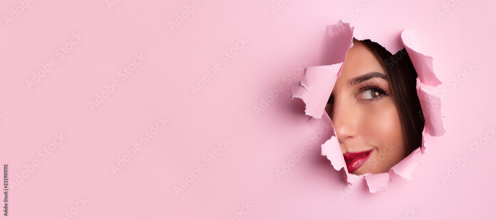 Fototapeta Beauty salon advertising banner with copy space. Beautiful girl looks through hole in pink paper background. Make up artist, fashion, beauty concept. Cosmetics sale.