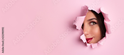 Obraz Beauty salon advertising banner with copy space. Beautiful girl looks through hole in pink paper background. Make up artist, fashion, beauty concept. Cosmetics sale. - fototapety do salonu