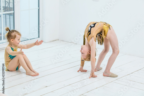 Foto op Canvas Gymnastiek Little gymnast girl girls and dancer doing stretching in bright room happy and cute