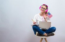 Young Woman With USA Flag Using A Laptop Computer On A Gray Background