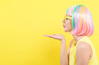 Woman in a colorful wig blowing a kiss on a yellow background