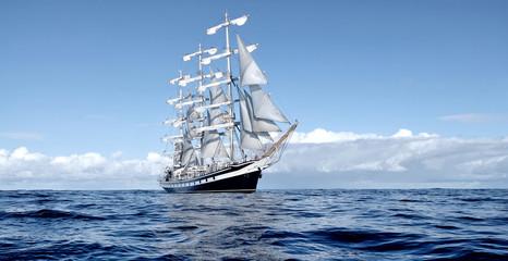 Sailing ship under white sails at the regatta