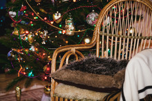Wicker Chair On Background Of Christmas Tree With Toys