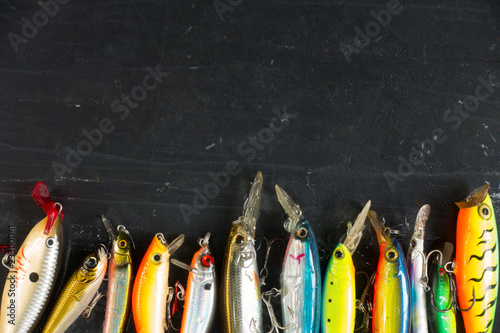 Cuadros en Lienzo Various of fishing lures colorful on black stone wet background.