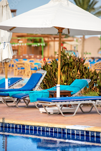 Swimming Pool with Deck Chairs and Beach Umbrellas