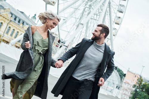 obraz dibond Romantic date outdoors. Young couple running at entertainment park holding hands looking at each other smiling happy