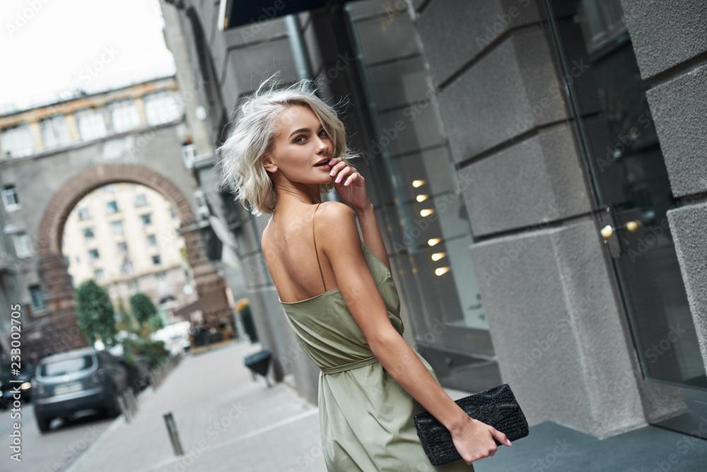 Fototapeta Fashion. Young stylish woman walking on the city street looking back camera smiling playful