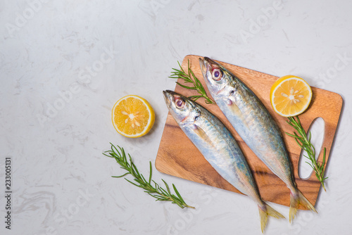Fresh raw fish decorated with lemon slices and herbs on wooden table Fototapeta