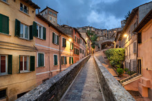 Perugia, Italy. Medieval Aqueduct And Colorful Buildings At Dusk