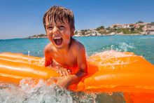 Excited Boy Having Fun Riding Waves In The Sea