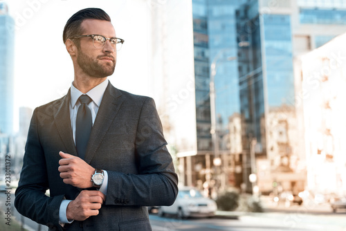 Valokuva  Close up profile portrait of a successful young bearded guy in suit and glasses