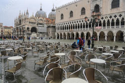 obraz lub plakat Venedig bei Hochwasser: Leere Tische und Stühle im Wasser am Markusplatz gegenüber dem Dogenpalast und Basilica San Marco