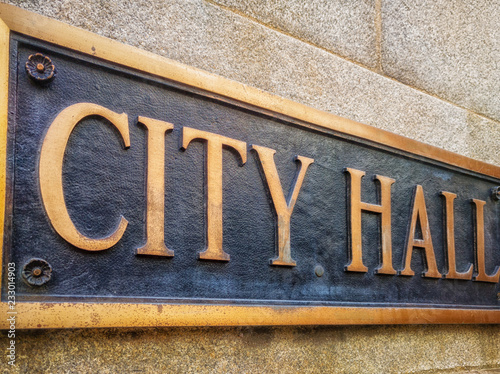 Photo Exterior sign that reads City Hall in brass letters