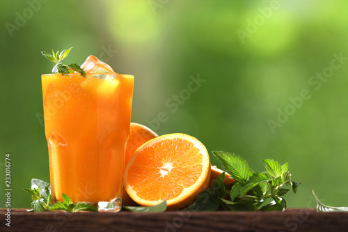 Foto auf Gartenposter Saft Fresh orange juice in glass with sliced orange on wood and nature background