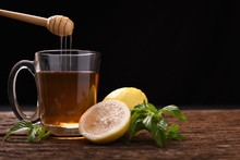 Hot Honey Lemon Tea In Glass With Mint And Sliced Lemon On Wooden Table And Black Background