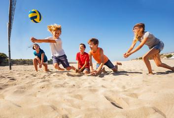 Boy making bump pass during beach volleyball game
