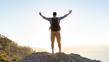 Hiker With Arms Outstretched On Hill Top