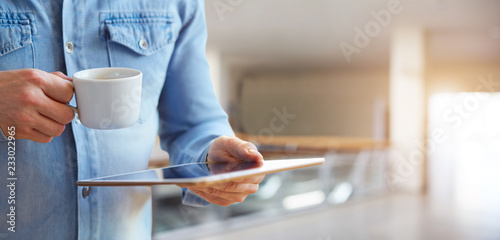 Male hands holding white digital tablet and cup of coffee