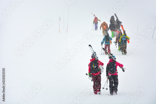 skiers carries skis and equipments to the track on a slope for skiing on Mount Asahi (Asahidake mountain) during snowfall on winter day, Hokkaido, Japan