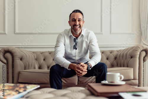 Businessman sitting on couch of hotel room Fototapet