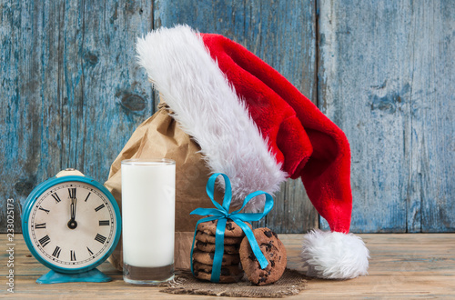 Milk and cookies for Santa Claus and Santa's hat over wooden background.