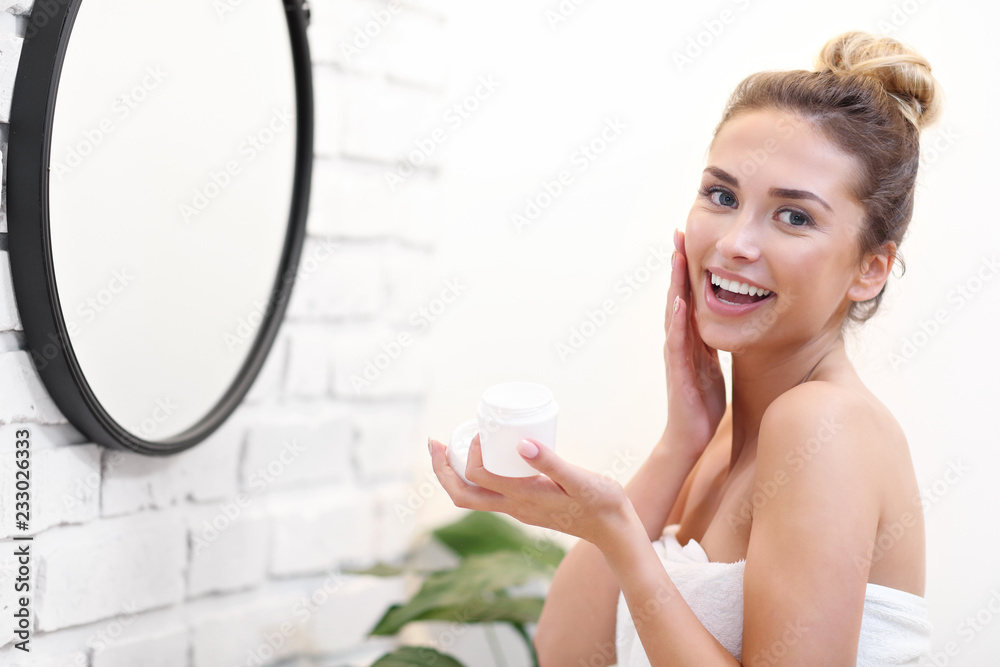 Fototapeta Young woman cleaning face in bathroom mirror