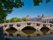 canvas print picture - Alte Brücke mit Blumen spiegelt sich im Wasser