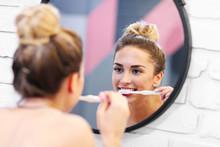 Young Woman Brushing Teeth In ...
