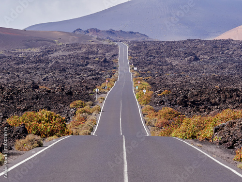 Fototapety, obrazy: Empty endless highway through the volcanic landscape of Lanzarote island, Canary islands, Spain