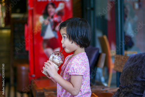 Fotografie, Obraz  Portriat Asian little girl drinking blended ice chocolate with funny face