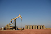 Complete Crude Oil Well Site. Pump Jack And Production Storage Tanks, Wyoming, With Copy Space.