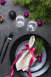 Christmas or New Year table setting with christmas pine branches, holiday decorations knife, fork ,ribbon and plate. Menu concept on dark background