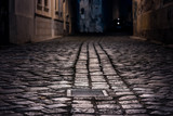Fototapeta Uliczki - Empty alley paved with wet cobblestone at night illuminated by street lamps with a sewer cap in focus