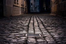 Empty Alley Paved With Wet Cobblestone At Night Illuminated By Street Lamps With A Sewer Cap In Focus