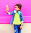 canvas print picture - Happy smiling child taking selfie by smartphone in city on colorful wall background