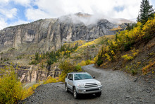 Exploring Autumn Mountains - On A Cloudy And Foggy Autumn Day, A 4X4 SUV Is Exploring In Colorful Autumn Mountains On Winding Black Bear Pass Trail, Near Telluride, CO, USA.