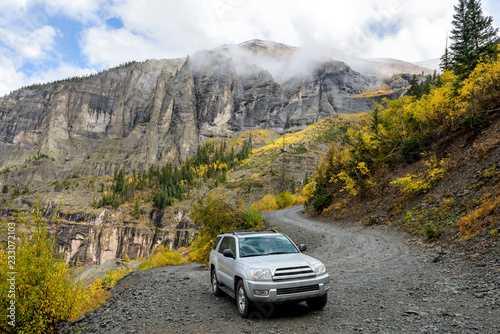 Fotografie, Obraz  Exploring Autumn Mountains - On a cloudy and foggy autumn day, a 4X4 SUV is exploring in colorful autumn mountains on winding Black Bear Pass trail, near Telluride, CO, USA