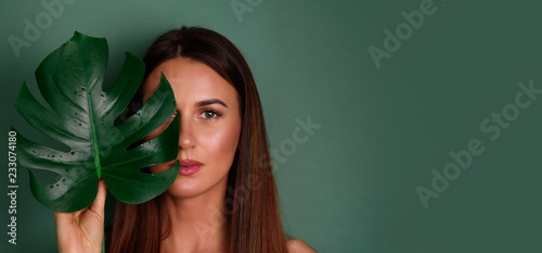 Fotografía Young woman with natural make up and tropical monstera leaf in hand over green background with copy space