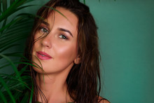 Young Girl With Wet Hair, Natural Make Up Between Tropical Palm Leaves On Green Background. Banner, Copy Space. Skin Care, Pure Beauty, Body Treatment, Fashion, Cosmetics Concept.