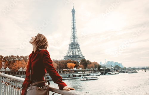 Obraz Style redhead girl in red coat and bag at parisian street with view at Eiffel tower in autumn season time - fototapety do salonu