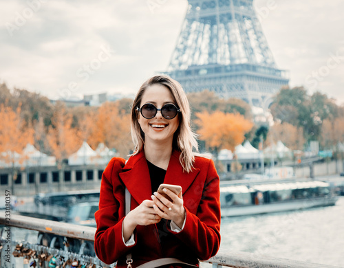 Style redhead girl in red coat make a photo on parisian street in autumn season time. Eiffel tower on background Wall mural